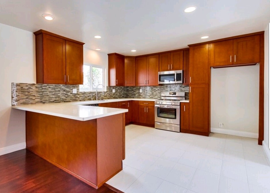 Remodeled Kitchen White Countertops Red Wood Cabinets Stone Mosaic Wall | Best General Contractor for Kitchens in Los Angeles | High Class Builders