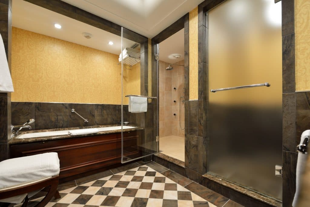 New Remodeled Bathroom Black and White Marble Tile Floor Bathtub and Shower with Yellow Wallpaper | Best General Contractor for Bathrooms in Los Angeles | High Class Builders