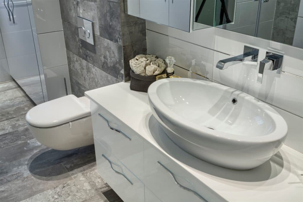 Remodeled Bathroom Sink Cabinets Grey Granite Stone Tile Wall | Best General Contractor for Bathrooms in Los Angeles | High Class Builders