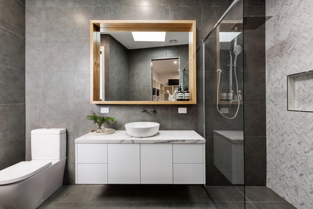 Remodeled Modern Bathroom Glass Shower Grey Stone Tile Wall White Sink Cabinets | Best General Contractor for Bathrooms in Los Angeles | High Class Builders