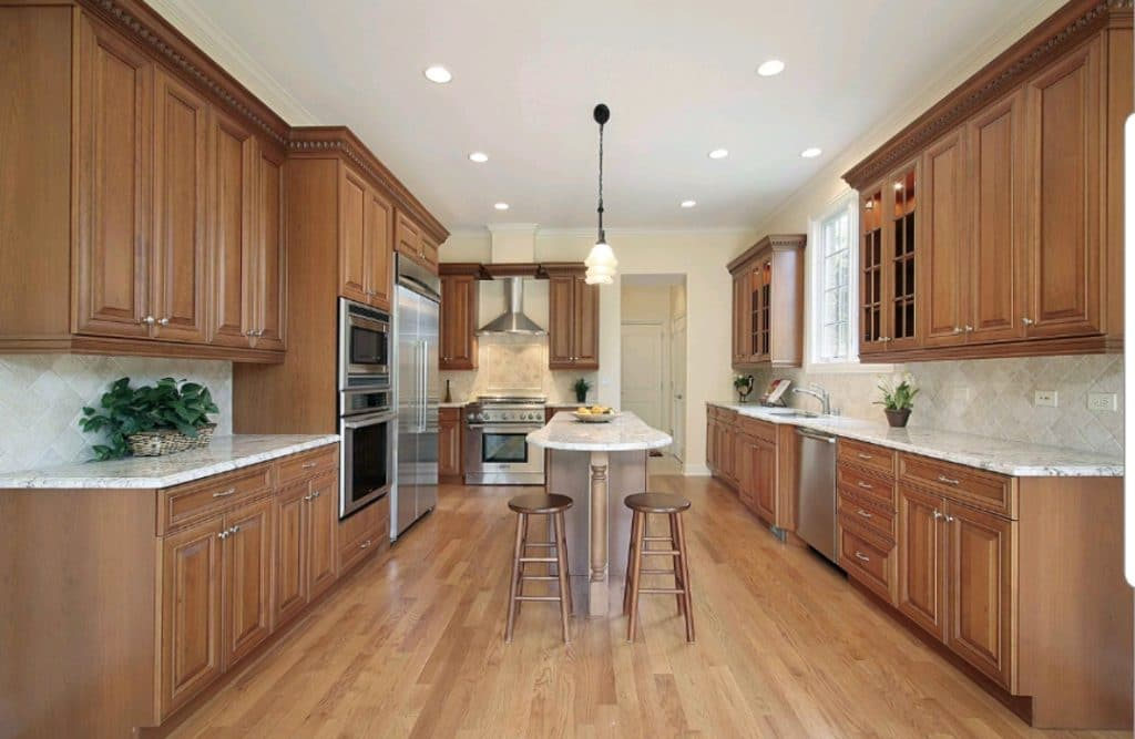 Remodeled Classic Kitchen White Marble Countertops Brown Wood Cabinets Stools | Best General Contractor for Kitchens in Los Angeles | High Class Builders