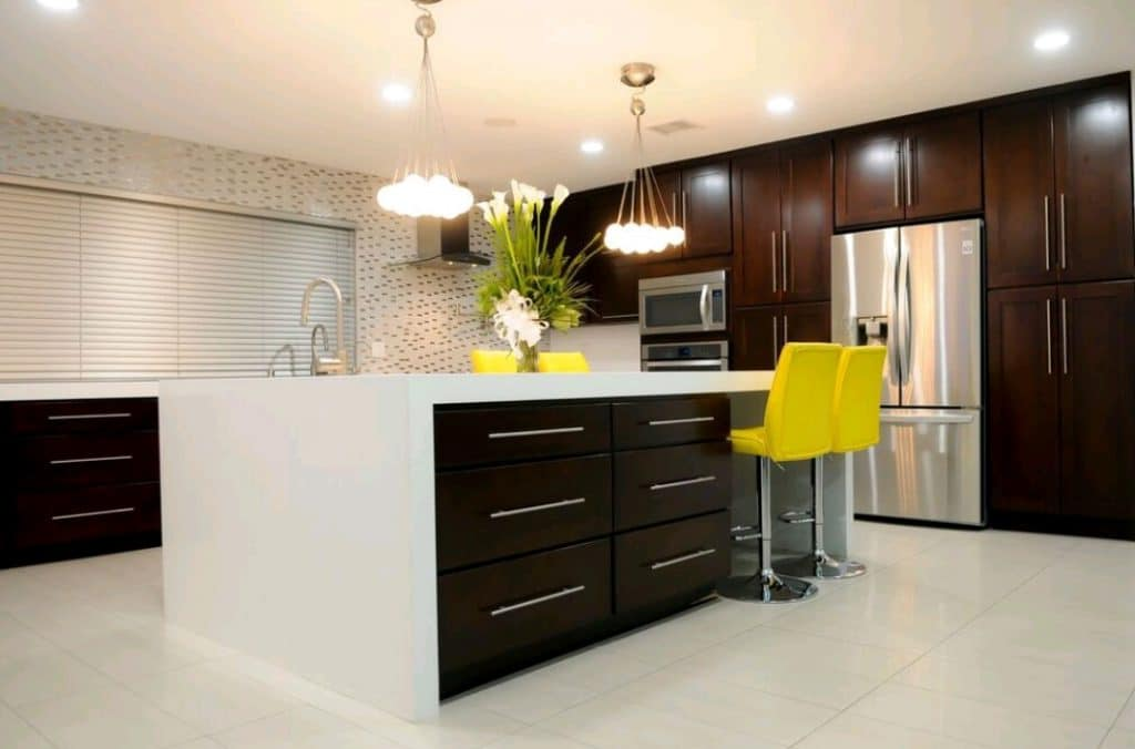 Remodeled Kitchen White Waterfall Granite Countertops Dark Brown Wood Cabinets Yellow Stools | Best General Contractor for Kitchens in Los Angeles | High Class Builders