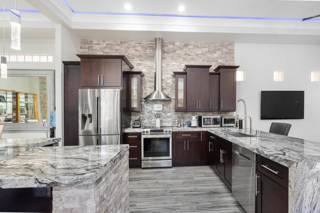 Remodeled Elegant Kitchen Granite Waterfall Countertops Dark Wood Cabinets | Best General Contractor for Kitchens in Los Angeles | High Class Builders