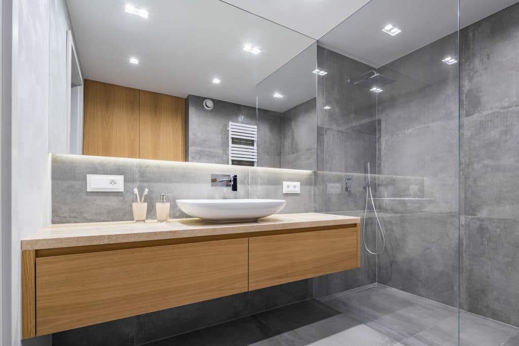 Modern Bathroom Glass Shower Hardwood Cabinets Grey Polished Concrete Floor Wall | Best General Contractor for Bathrooms in Los Angeles | High Class Builders