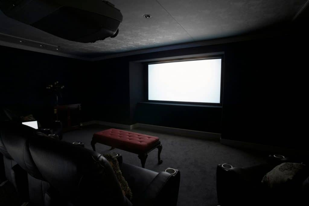 New Home Entertainment Theatre Room Construction with Leather Cinema Seats and Red Ottoman | Best General Contractor for Home Entertainment Systems in Los Angeles | High Class Builders