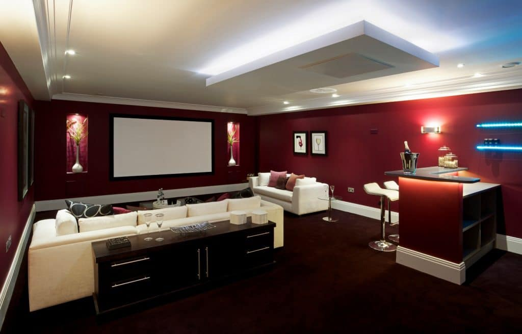 New Home Entertainment Theatre Lounge Construction with White Couches Red Wallpaper and Lighting | Best General Contractor for Home Entertainment Systems in Los Angeles | High Class Builders