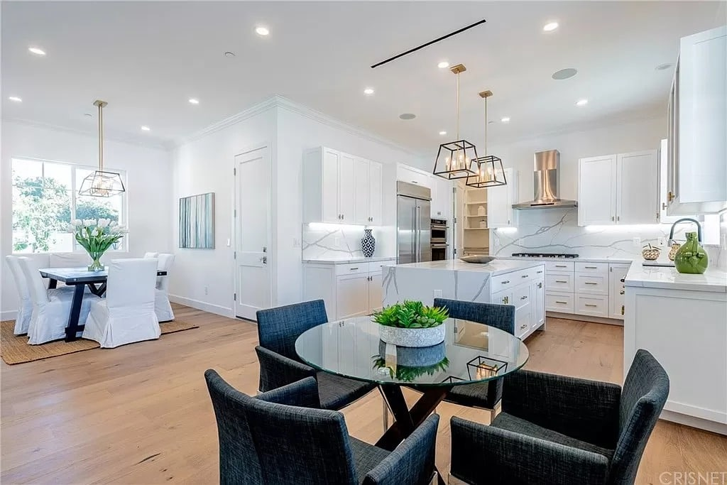 Modern Kitchen Dining Room Marble Waterfall Counter White Dark Grey Chairs Glass Table | Best General Contractor for Kitchens in Los Angeles | High Class Builders